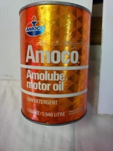 AMOCO AMOLUBE MOTOR OIL FULL QUART CAN SHOWS SOME WEAR, ORANGE PAINT RUBBED OFF IN SPOTS, LIGHT WEAR ON TOP RIM, LIGHT PITTING ON TOP, MOSTLY CLEAR, BOTTOM RIM HAS SLIGHT DENT, LIGHT TARNISH, BOTTOM IS CLEAR