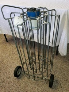 ROLLING OIL RACK, IN GOOD CONDITION WITH 8 SECTIONS AROUND CENTER SECTION, EACH SECTION HOLDS 5 CANS