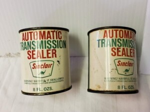 (2) SINCLAIR AUTOMATIC TRANSMISSION SEALER FULL 8 FL. OZ. CANS, 1ST CAN COLOR IS BRIGHT WITH RUBS AND SCRATCHES, TOP RIM IS WORN, TOP IS WORN WITH PITTING, LOWER RIM IS WORN WITH LIGHT PITTING, BOTTOM IS WORN WITH LIGHT PITTING AND RUST -- 2ND CAN WRITING