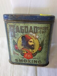 "VINTAGE TOBACCO TIN - BAGDAD SHORT CUT PIPE SMOKING, SIZE 3.75"" TALL x 3.5"" WIDE x 1"", BACKGROUND SHOWS NUMEROUS SCRATCHES, FADING, PAINT SCRATCHED OFF AND WORN, ENDS SHOW WEAR WITH SCRATCHES, LIGHT PITTING, SHOWS RUST NEAR LOWER RIM, BOTTOM SHOWS RUST AN"